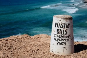 """A concrete cylinder sits on the right of the shot, in front of ocean waves. The cylinder has """"plastic kills! El plastico mata !"""""""