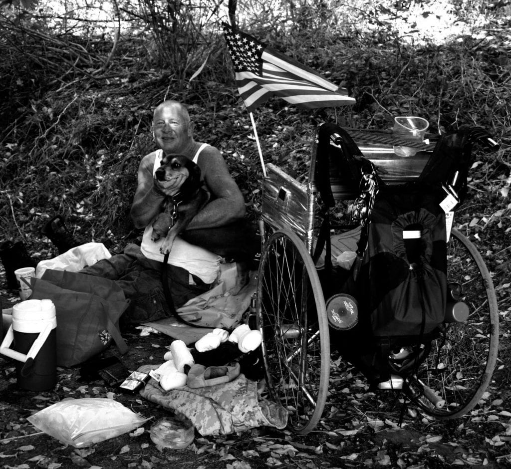 A homeless man with disabilities sits on the ground with his dog. His wheelchair is next to them, along with all his items and an American flag.