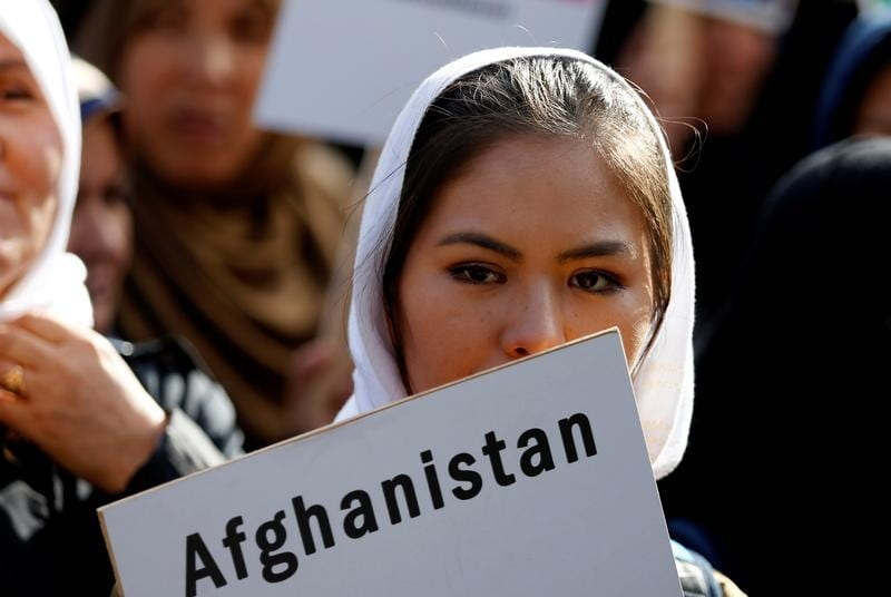 "A woman with a white headscarf holding a poster that says ""Afghanistan"""