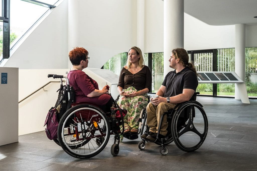 Three people in wheelchairs face each other while talking.