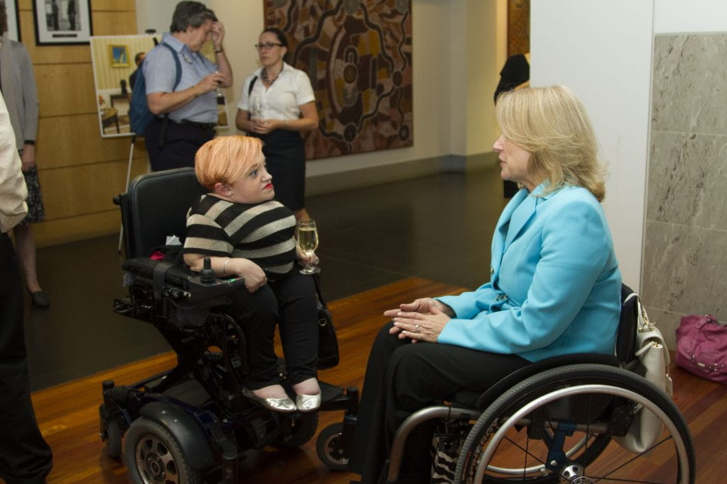 Disability activist Stella Young chats with Paralympic medalist Ann Cody. Both women use wheelchairs.