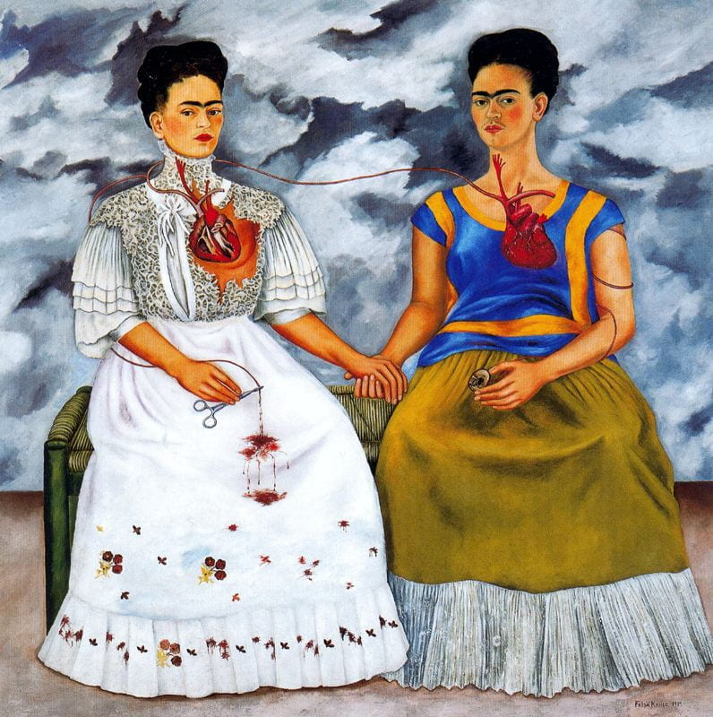 A painting by Frida Kahlo features two versions of herself side by side. One is in a white dress, the other in a blue top and green skirt. Both Fridas' hearts are visible, and connected by a vein.