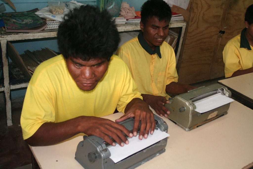 Kiribati 2009. A blind man sitting at a Braille machine