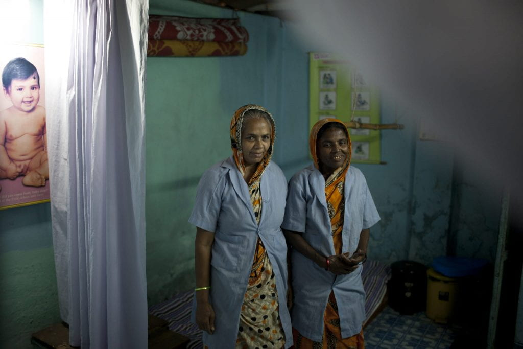 Two midwives stand next to a curtain in a dim room with photos of babies on the walls.