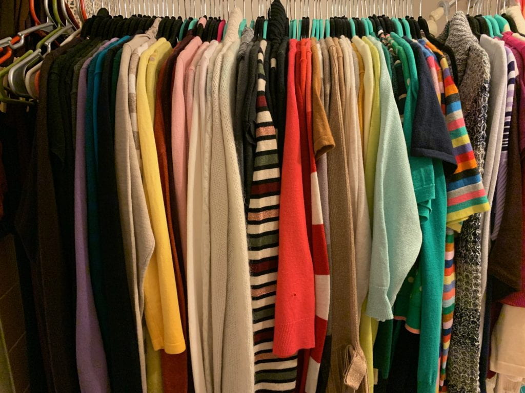 a photo of clothes hanging in a closet