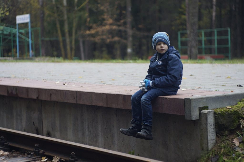 a lone little boy sitting on a platform