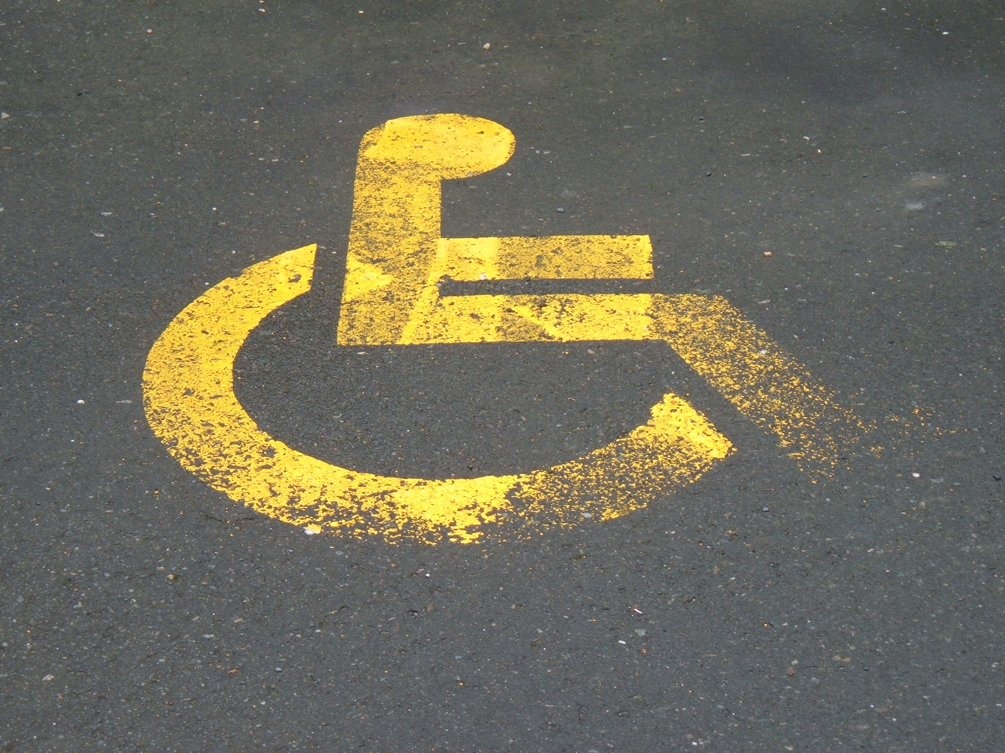 The symbol for handicap parking in yellow paint on black pavement.