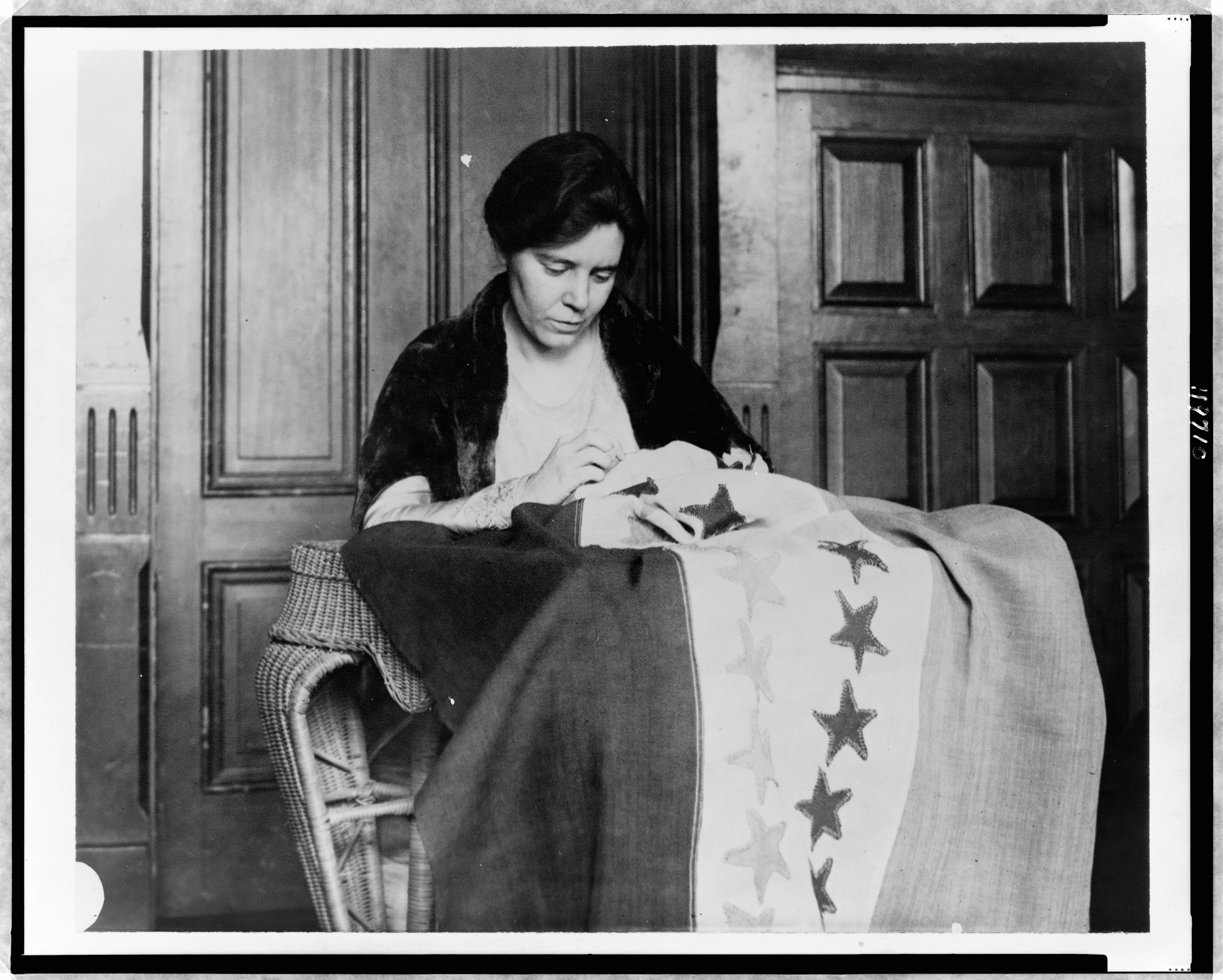 a photo of Alice Paul sewing the Suffrage flag