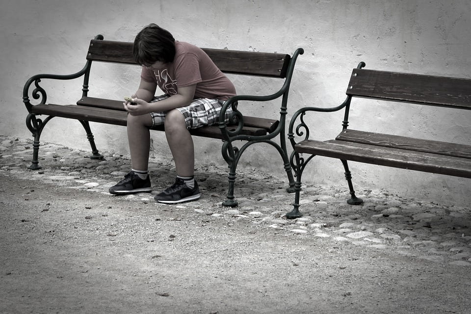 a picture of a young boy sitting alone on a park bench