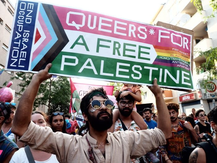 """A man holds a rainbow Pride protest sign with phrases including """"End Israeli occupation"""", """"Queers for a free Palestine"""", and """"Fight against: racism, Islamophobia, homo/transphobia, antisemitism, apartheid"""""""