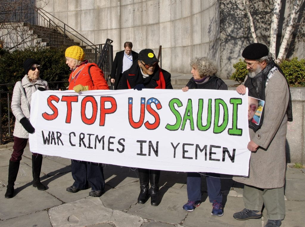 "Group holding sign Reading ""STOP US SAUDI WAR CRIMES IN YEMEN"""