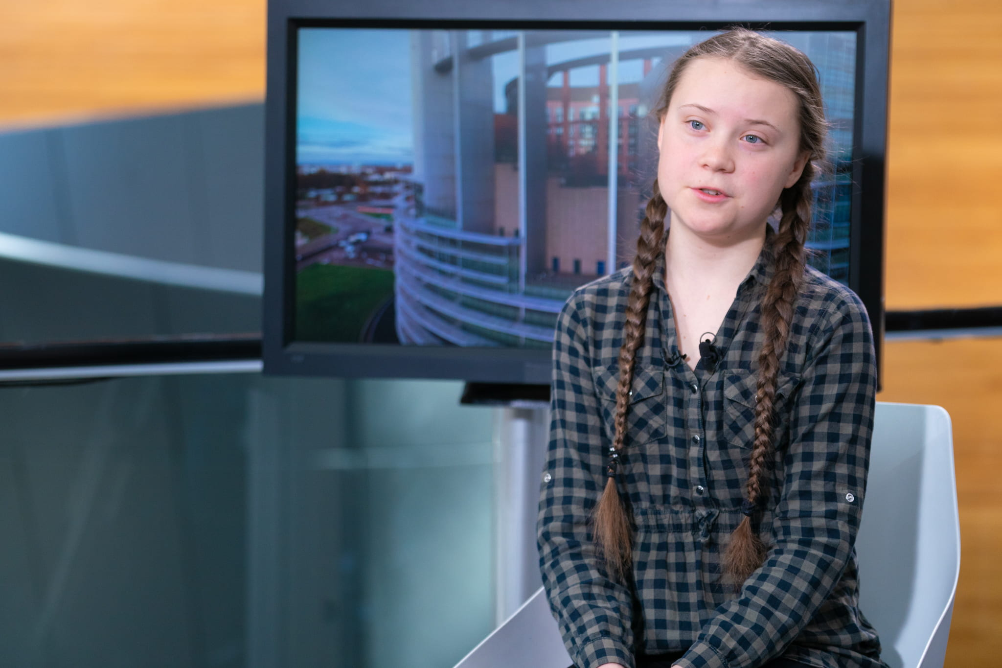 Greta Thunberg sitting in a chair and being interviewed.