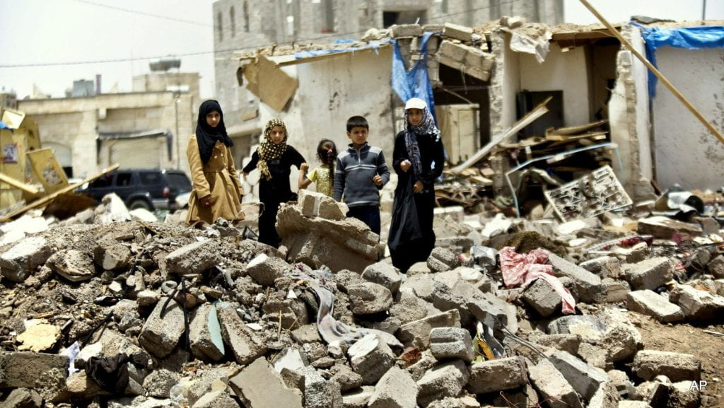 Children standing over ruins in Yemen.