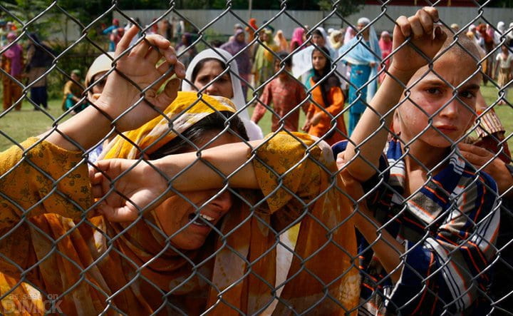 Devastated Kashmiri girls crying while holding on to fence