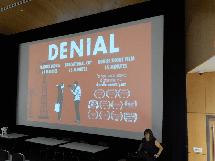 "Christine Hallquist, in front of a screen showing her film ""Denial"" talking to the audience."