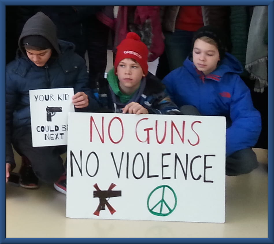 An image of three kids surrounding a sign that says No Guns No Violence.