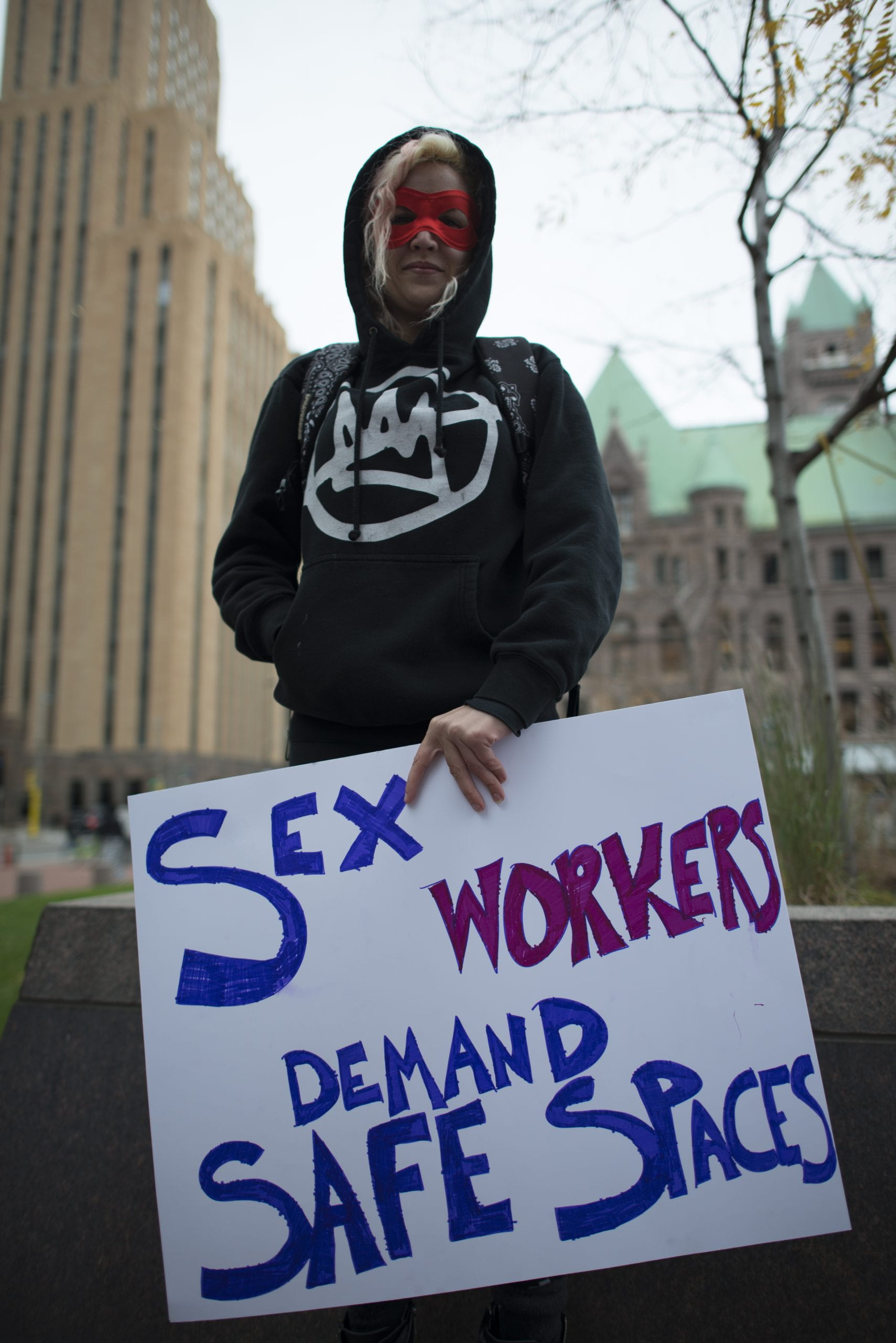 "Woman holding poster reaing ""Sex Workers Demand Safe Spaces"""