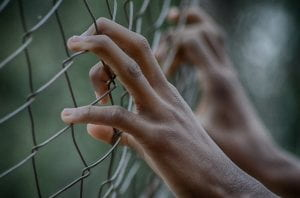 A pair of young hands gripping a prison fence