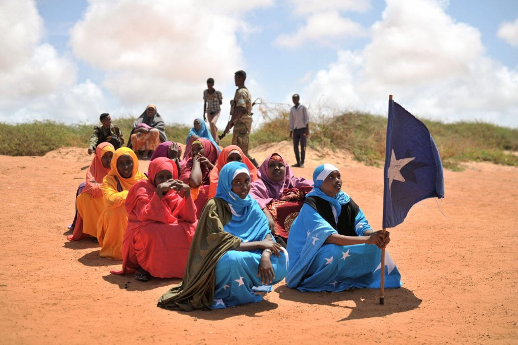 A young woman holds the Somali flag during a demonstration by a local militia, formed to provide security in Marka, Somalia