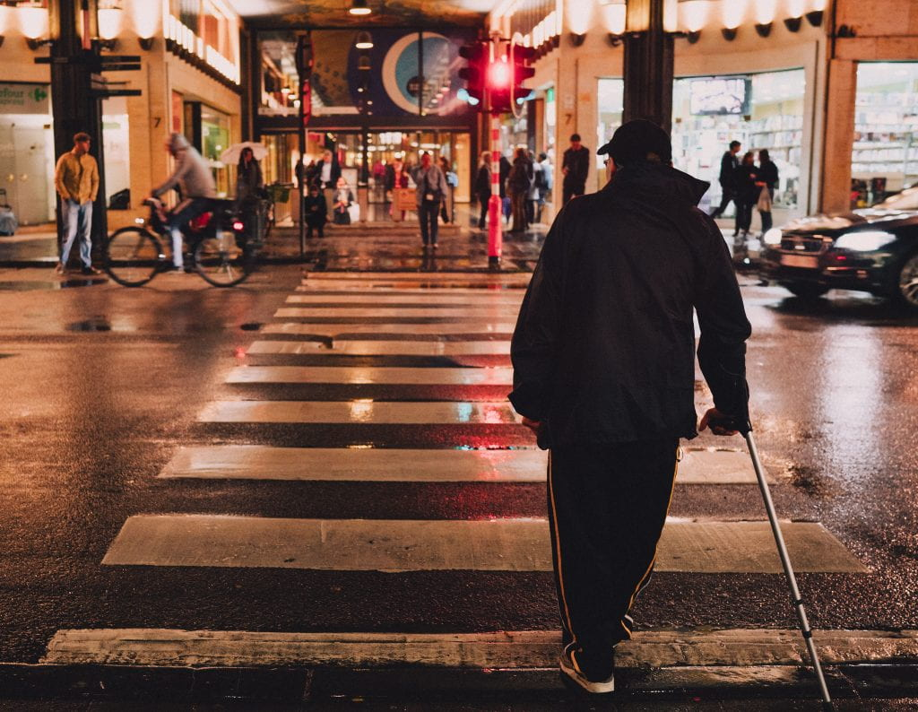 A man in dark clothing crosses a city street with the aid of a walking stick / mobility device of some sort.