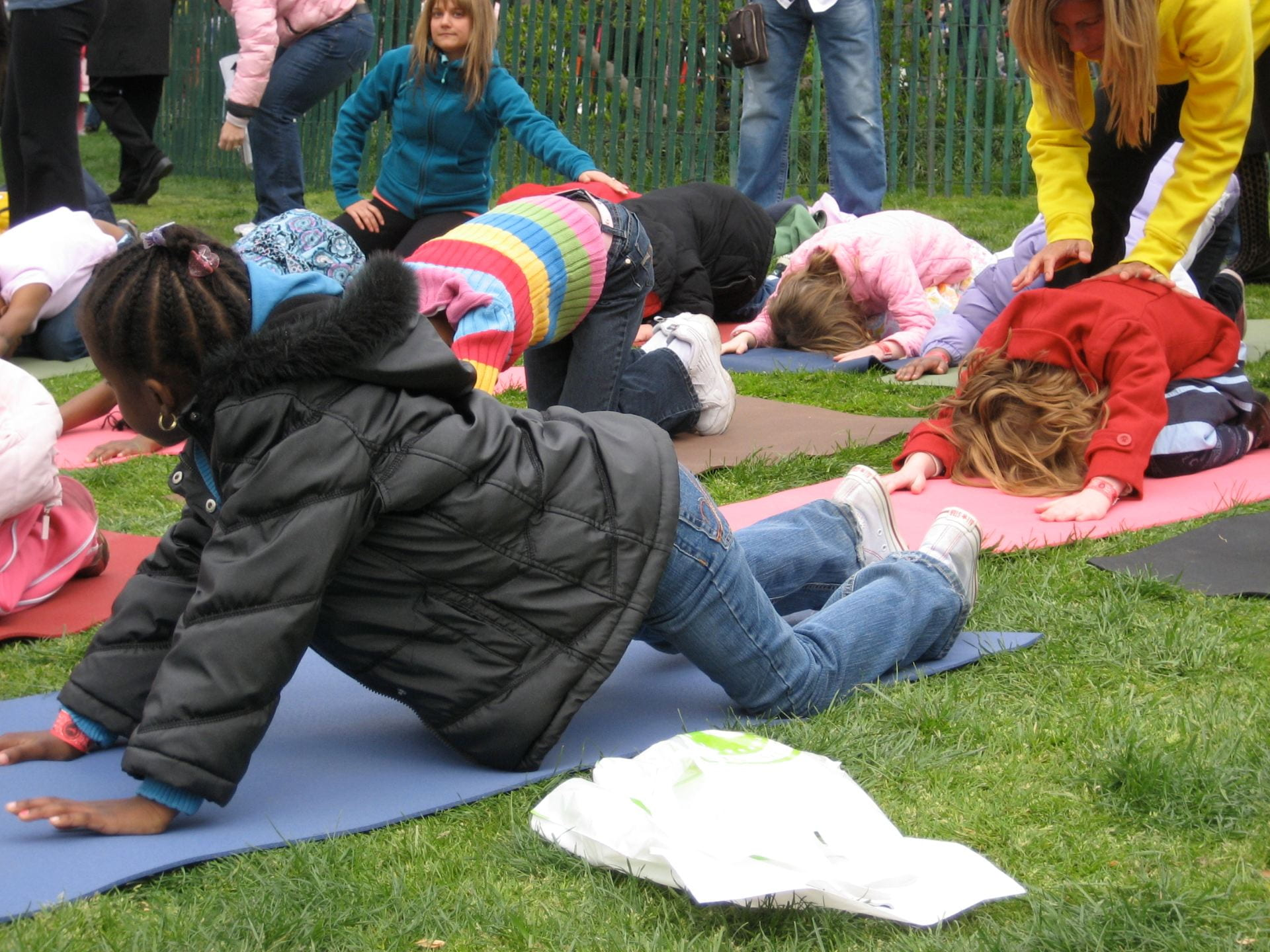 Children learning yoga outside.