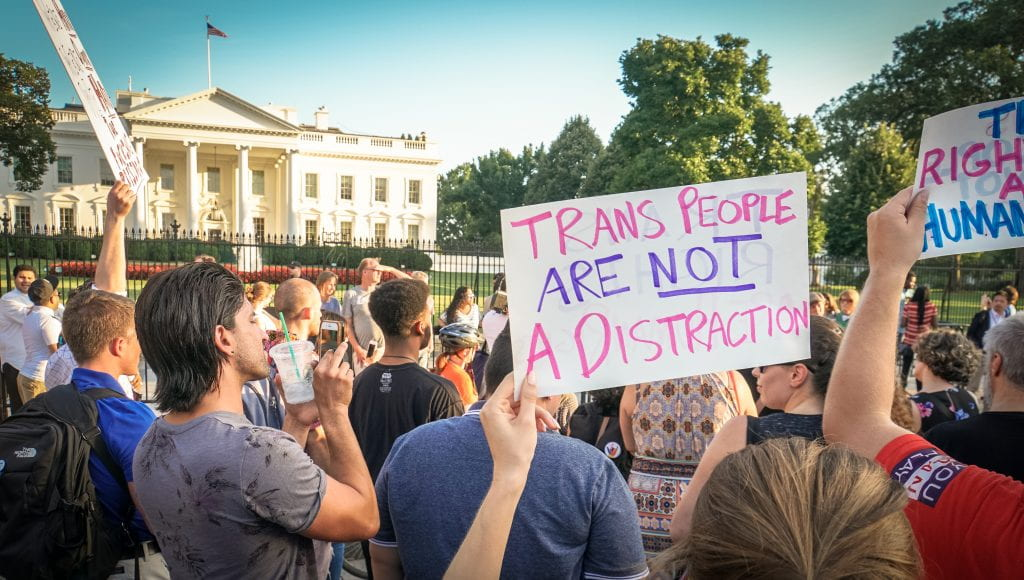 "Protesters hold a sign in front of the White House stating ""Trans people are not a distraction"""