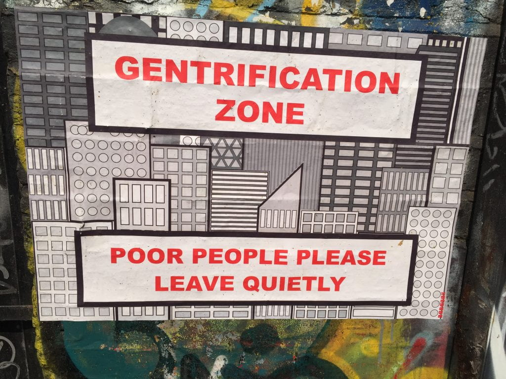 "a sign that reads ""Gentrification Zone, Poor people please leave quietly"""