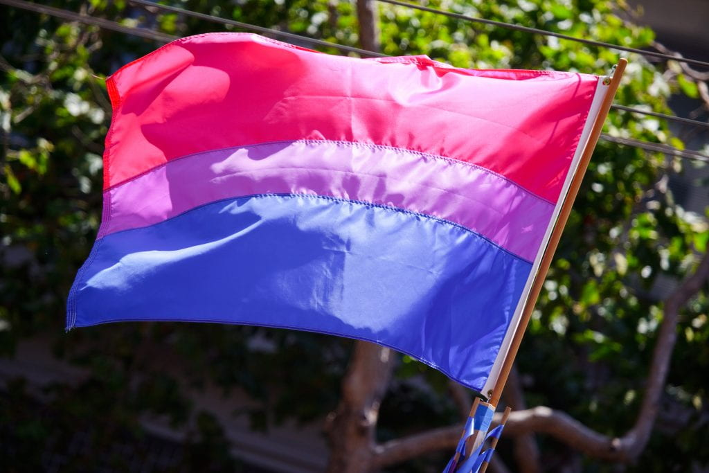 A pink, purple, and blue flag flies to represent bi pride.