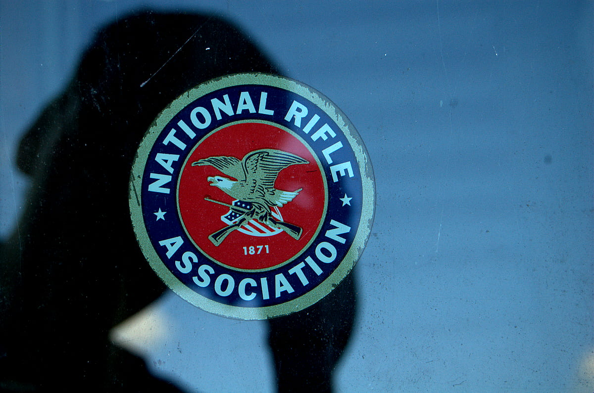 A man photographs the National Rifle Association logo.
