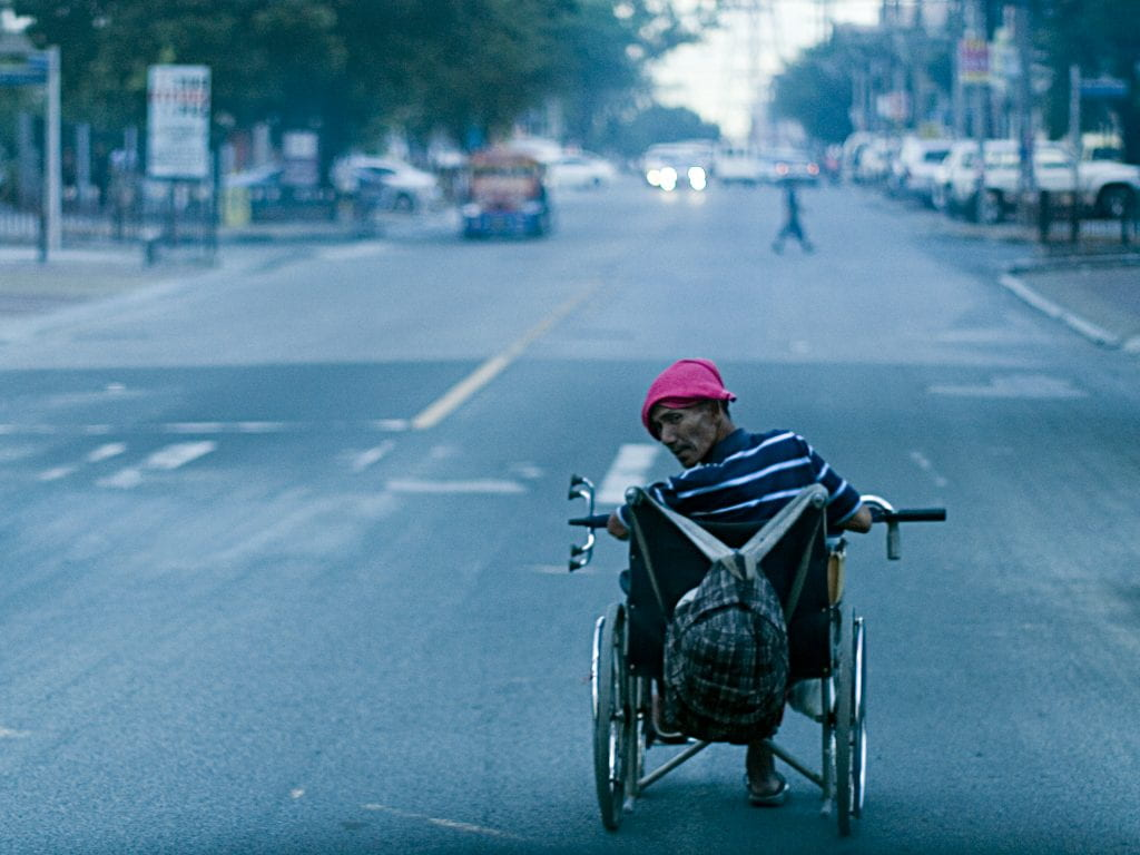 A man in a wheelchair looks back as he wheels down the street. He is wearing a bright pink hat and has a backpack hanging off the handles of his chair.