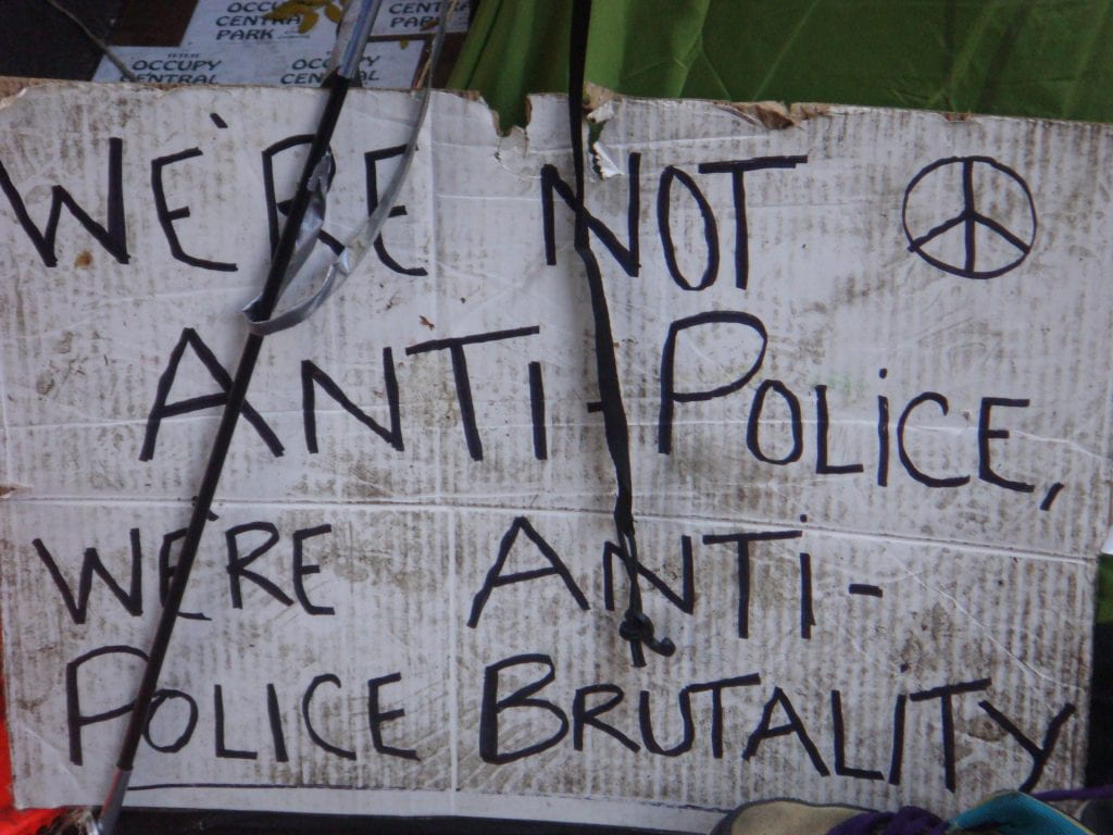 "a cardboard sign that reads ""We're not anti-police, we're anti-police brutality"""