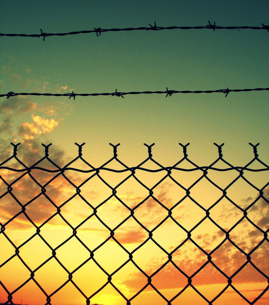 a picture of a sunset through a barred wire fence