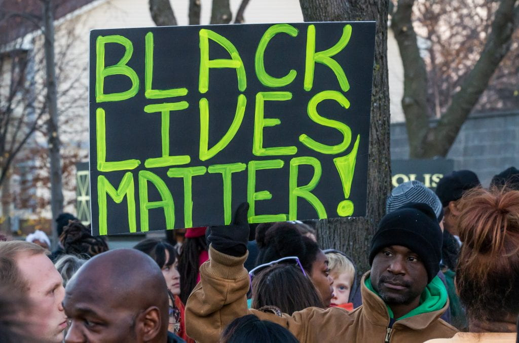 "An activist holds a ""Black Lives Matter"" signs outside the Minneapolis Police Fourth Precinct building following the officer-involved shooting of Jamar Clark on November 15, 2015. Source: Tony Webster, Creative Commons"
