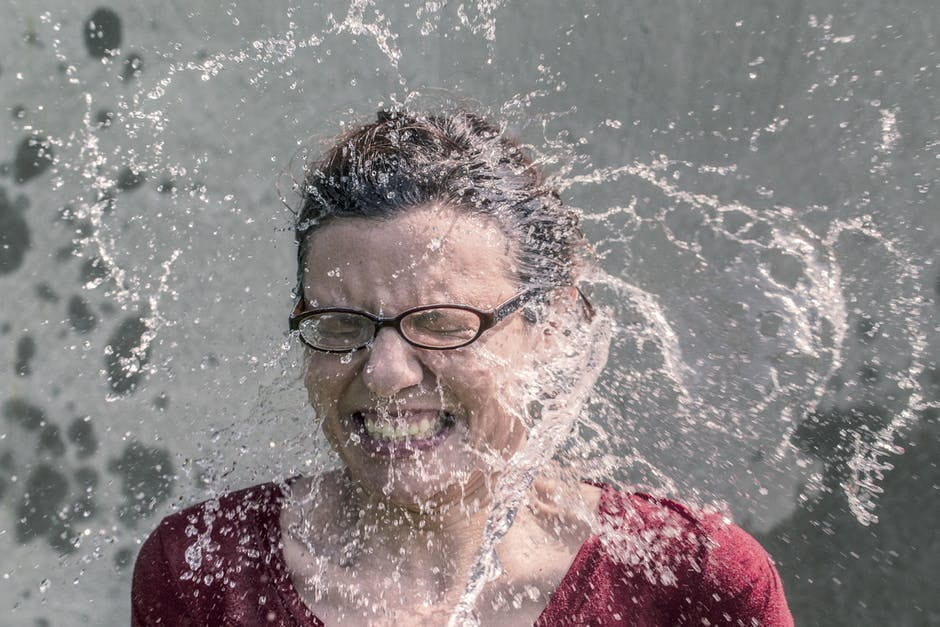 An image of a woman reacting to a splash of water from the top of her head. Basically a standard reaction from when someone does the Ice Bucket Challenge.