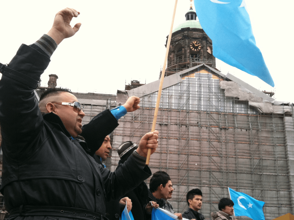 an Uyghur group holds their native flag while protesting repression against the Uyghur people