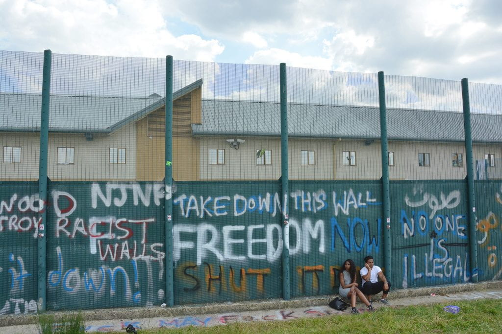 "A couple sits next to a large wall with graffiti saying ""Freedom,"" and ""Take down this wall!"""