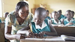 A teacher looks on as a young African girl does her school work.