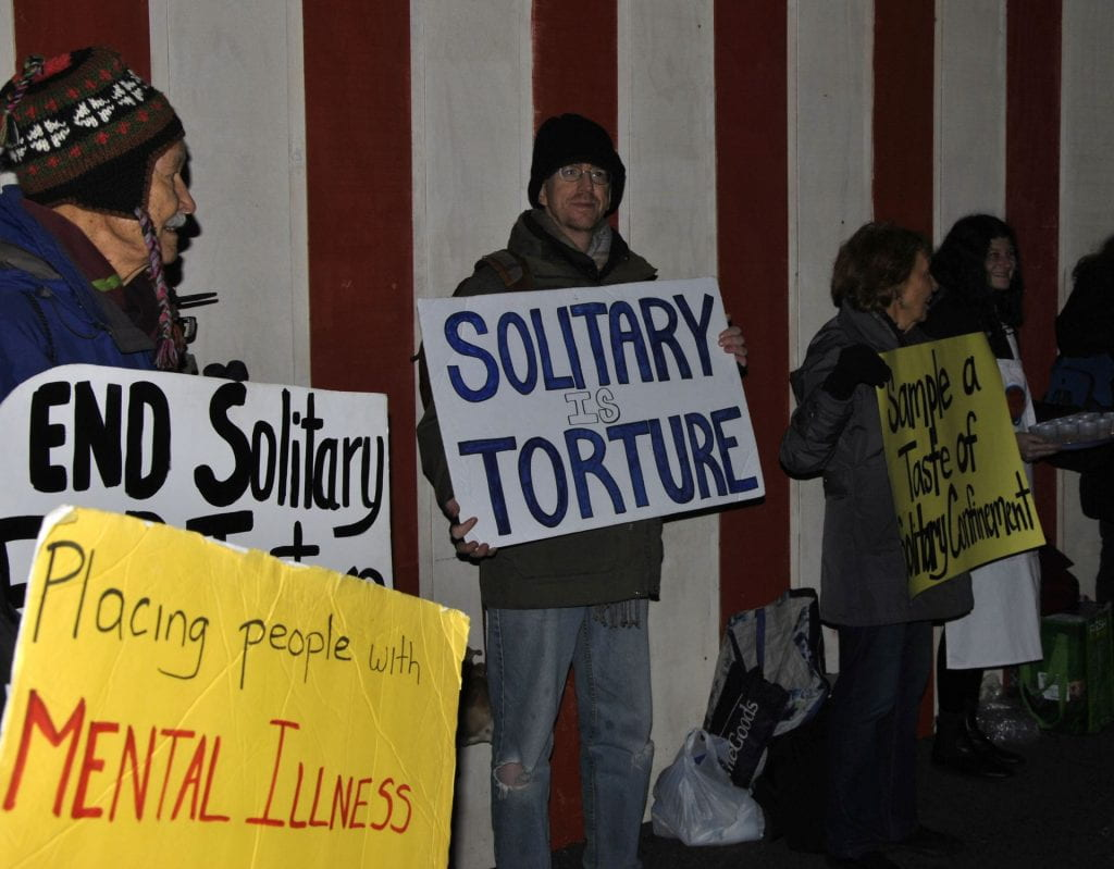 Image of protesters of solitary confinement holding signs connecting solitary confinement to torture and mental illness.