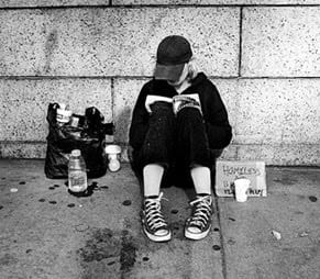 "A homeless student, sitting on the sidewalk against a wall, reading a book. The student has a small bag of items beside him and a sign that says, ""Homeless."""