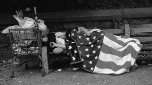 A homeless man sleeps under an American flag blanket on a park bench in New York City.
