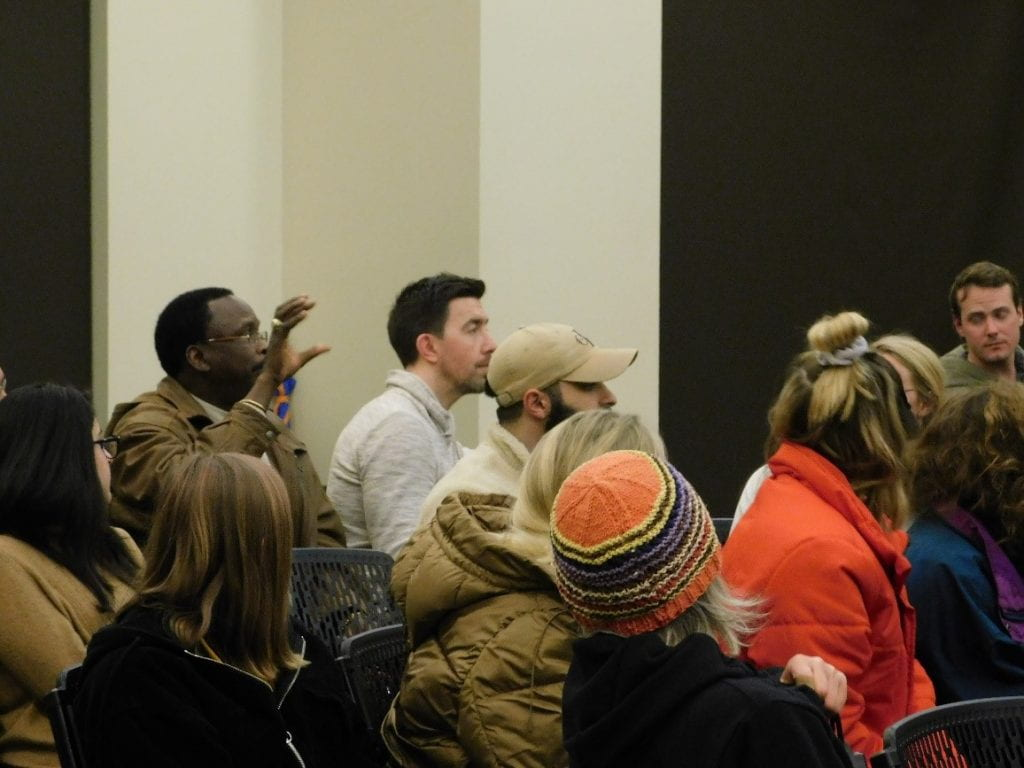 This is a picture from the event with an audience member asking the speakers a question.