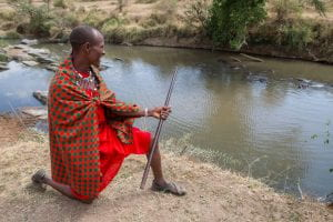 A Maasai man in traditional red clothing overlooks the Sekenani River. Nearby vegetation reflects off the water's rippled surface.