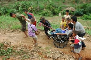 a group of young children help push a man in a wheelchair up a dirt road