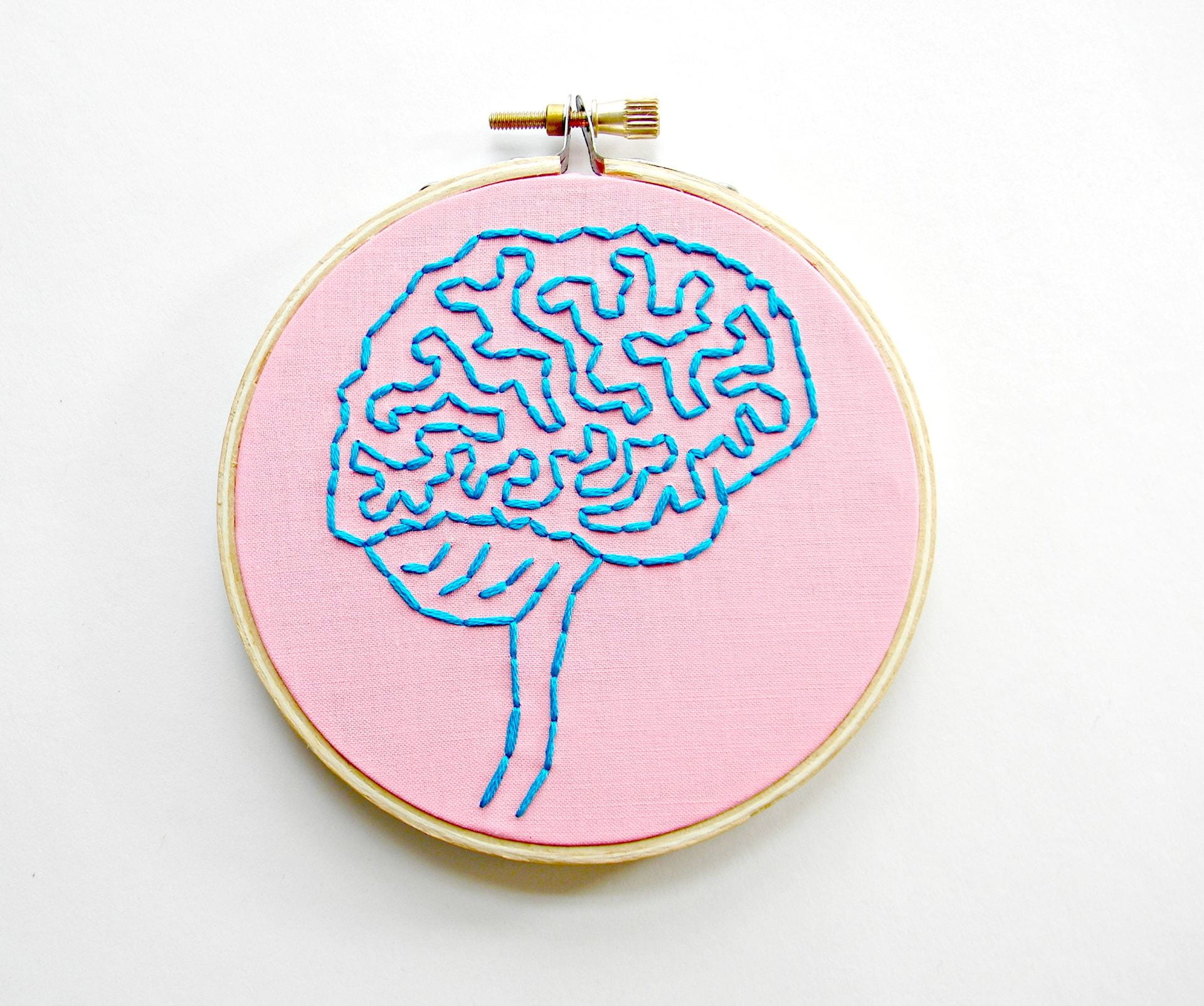 An image of a brain embroidered on a piece of fabric in an embroidery hoop.