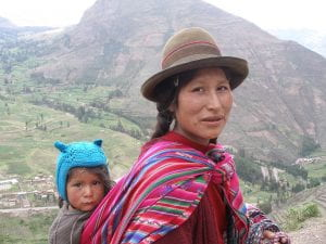 Indigenous Peruvian woman carrying her child on her back with mountains in the background