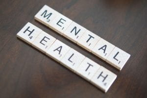 "Scrabble pieces spell out the words ""mental health."""