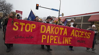 "An image of protesters holding up a banner with the words ""STOP DAKOTA ACCESS PIPELINE"" across it."