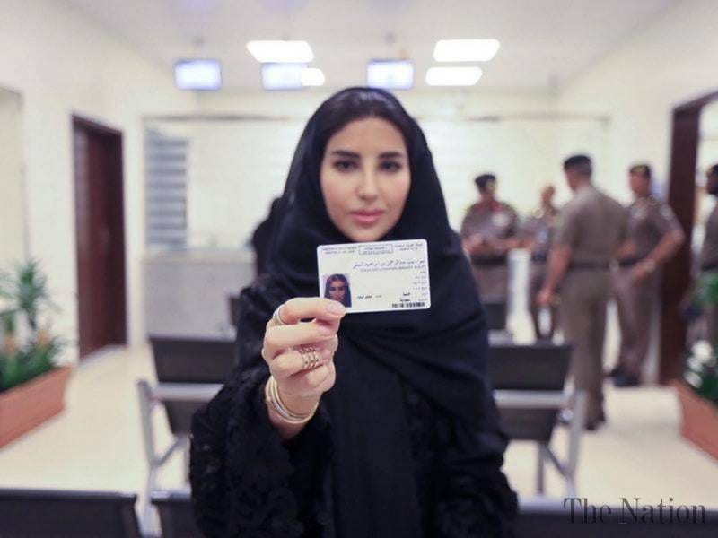 An image showing a Saudi Arabian woman holding up her driving license.