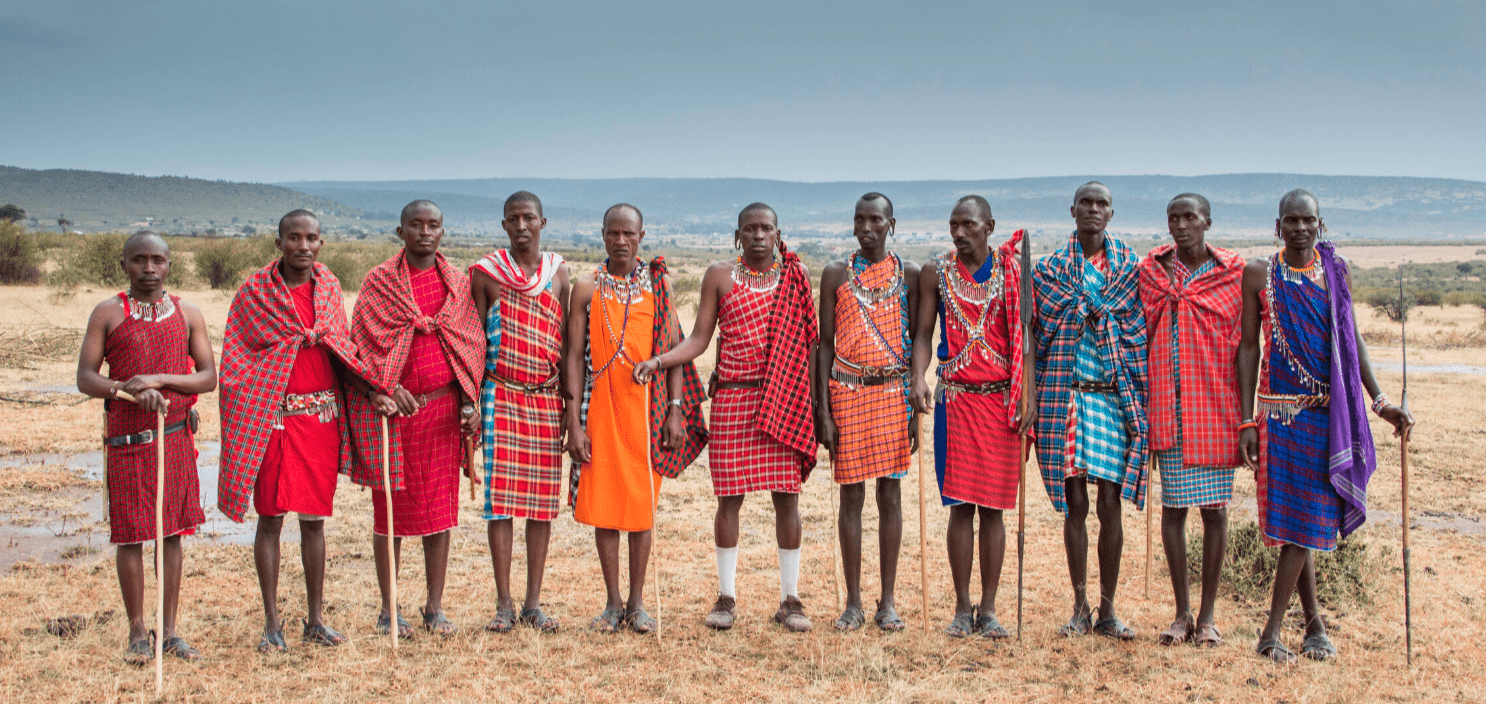Photo showing Maasai men standing next to each other in a field.