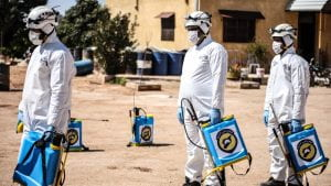A photo of 3 medical professionals in masks and white suits carrying testing machines in war-torn Syria